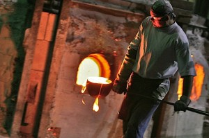 A worker carries a ladle of molten glass from the furnace